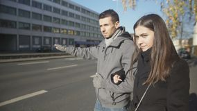 Young couple standing near road, man unconfidently catching taxi, hitchhiking stock footage