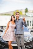 A young couple is standing near their new used car. Happy family bought a used car. Concept of buying a used car or a rental car Stock Photos