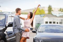 A young couple is standing near their new used car. Happy family bought a used car. Concept of buying a used car or a rental car Royalty Free Stock Images