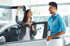 Young Couple Standing Near then New Car and Holding a Key Stock Image