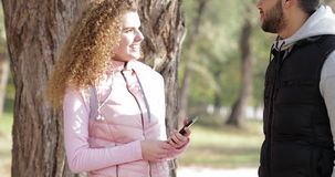 Young Couple Standing Near Tree Speaking Handsome Man And Pretty Curly Woman Outdoor Morning Sunrise Autumn Park. Natural Light Slow Motion 60 stock footage