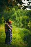 Young couple standing near water. Young happy couple standing near water in green forest, looking ahead. Man holding woman. Woman wrapped in a plaid, happy and Royalty Free Stock Image