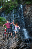 Young couple standing near waterfall with their bikes Royalty Free Stock Photography