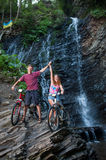 Young couple standing near waterfall with their bikes Royalty Free Stock Images