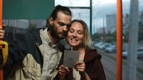 Young couple standing near the window in tram or bus and reading from the card. Man and woman using public transport. Young beautiful couple standing near the stock footage