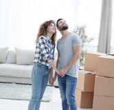 Young couple standing in new apartment and looking up Royalty Free Stock Photo