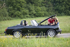 A young couple standing next to their broken down sports car speaking on a mobile phone Stock Photography
