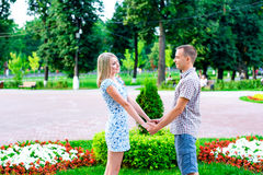 Young couple standing in park ribbon holding each other`s hands, a declaration of love,  gentle hug, concept  fami Royalty Free Stock Images