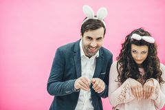 Young couple standing on pink background. With a bunny ears on the head. Beautiful, macho or boyfriend and cute girl stock photo