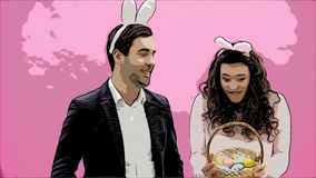 Young couple standing standing on pink background. With bunny ears on the head. During this man gives his wife a basket stock video