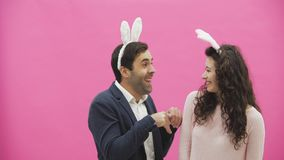 Young couple standing standing on pink background. During this, they carry out the movement of rabbits. The woman put. Her hands on his neck, choking. After stock video footage