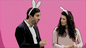 Young couple standing standing on pink background. During this, they carry out the movement of rabbits. The woman put. Her hands on his neck, choking. After stock video