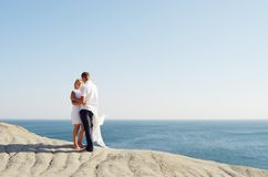 Young couple standing on rock by the sea Stock Photography