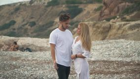 Young couple standing at the rocky sea cost talking in slow motion, Man and woman cuddle each other tenderly, their hair. Fluttering. Leisure of young happy stock footage