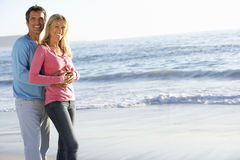 Young Couple Standing on Sandy Beach Stock Image