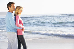 Young Couple Standing On Sandy Beach Looking Out To Sea stock photos