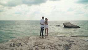 Young couple standing at the sea cost admiring beautiful seascape. Man and woman cuddle each other. Leisure of young. Young couple standing at the sea cost stock video