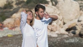 Young couple standing at the sea cost admiring beautiful seascape, Man and woman spend time together near rocky hill. Man points with his hand far away stock footage