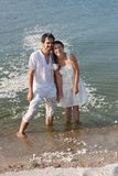 Young couple standing in the sea and laughing after the fight pillows Royalty Free Stock Photo