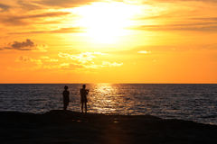 Young couple standing on the shore and looks at the setting sun Stock Image