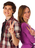 Young couple standing and showing victory gesture Stock Images
