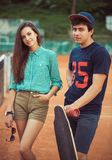 Young couple standing on a skateboard on the tennis court Stock Image