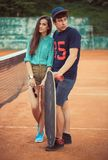 Young couple standing on a skateboard on the tennis court Royalty Free Stock Photos