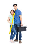 Young couple standing with spirit level measuring tool and tool box. On white background stock images