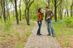 Young couple standing talking in a park Royalty Free Stock Image