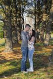 Couple pausing in the midst of trees for a little affection. stock images