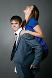 Young Couple Standing Together Against A Grey Wall Stock Photo