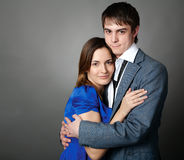Young couple standing together against a grey wall Stock Image