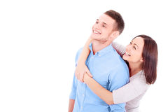 A young couple standing together, hugging and looking at somethi Royalty Free Stock Images