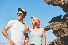 Young couple standing together by the rock looking away stock photo