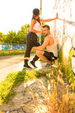 Young Couple standing at a wall in a urban environment Royalty Free Stock Image