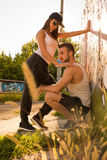 Young Couple standing at a wall in a urban environment Stock Photos