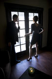 Young couple standing by window in dark room Stock Photography