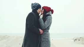 Young couple standing on the winter beach, rubbing his hands together. stock footage