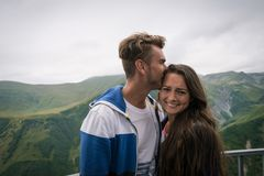 Young couple stands on background of beautiful green mountain royalty free stock photography