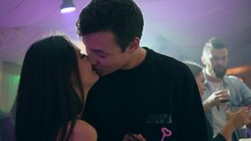 Young couple stands close together and kissing in intimate atmosphere on background of bright lights in club stock video