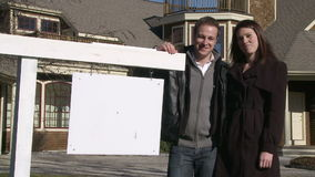 A young couple stands in front of Real Estate Sign. A young couple stands in front of their home with a generic sign stock video footage