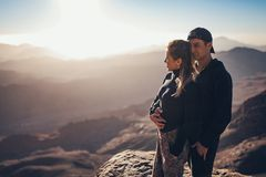 Couple stands, hugs and looks at sunrise in mountains. royalty free stock image