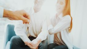 Young Couple Stare On The Key In Rieltors Hands. Bright Office. Keys In A Hand. Buying A Property. Panoramic Windows. Business Meeting. Customer And Buyer royalty free stock image