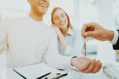 Young Couple Stare On The Key In Rieltors Hands. Bright Office. Keys In A Hand. Buying A Property. Panoramic Windows. Business Meeting. Customer And Buyer stock photos