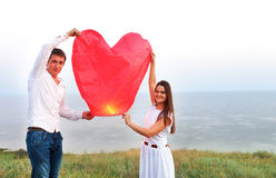 Young couple start a red Chinese sky lantern Stock Photo