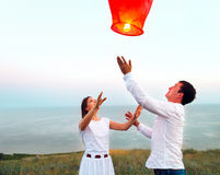 Young couple start a red Chinese sky lantern in the dusk Stock Photos