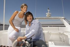 Young couple steering boat Stock Photography