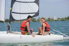 Young couple steering catamaran Stock Images