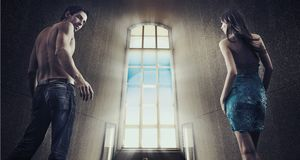 Young couple stepping into the window light Stock Photography