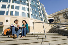 Young couple on steps studying, low angle view Royalty Free Stock Photography
